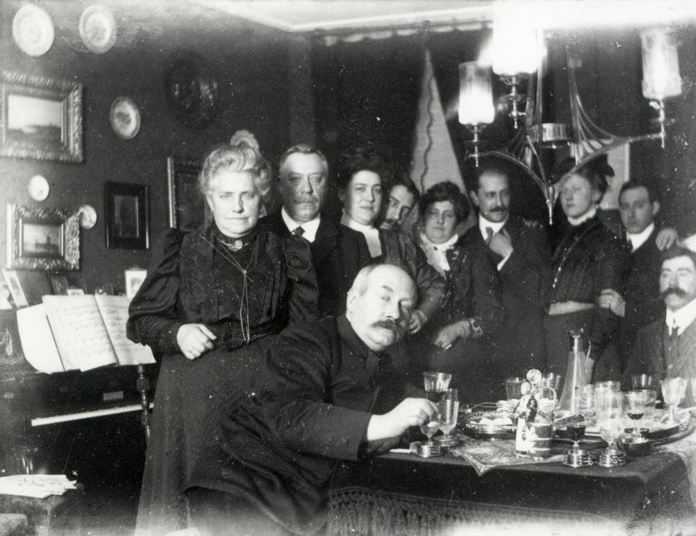 Groepsportret met Johannes Anthonius Moesman (voorgrond, 1859 - 1937) en familieleden in een kamer van zijn woonhuis Neude 7 te Utrecht.Moesman, Joh. A. (fotograaf/graficus/tekenaar)