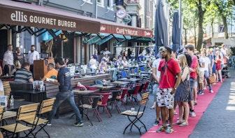 Tientallen mensen in de rij voor gratis hamburgers op de Neude