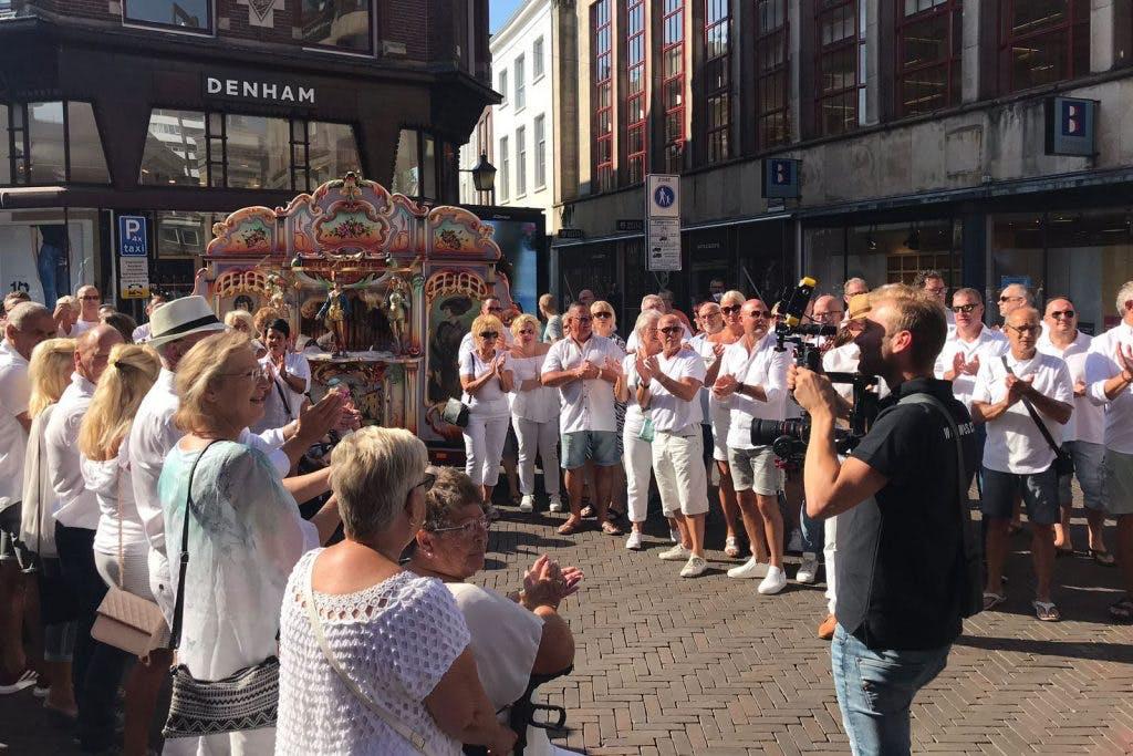 Honderd in het wit geklede mensen op Stadhuisbrug voor doodzieke Utrechtse volkszanger