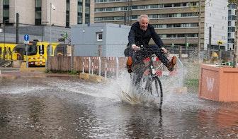 Foto's: Gigantische plas bij Jaarbeursplein zorgt voor natte voeten fietsers